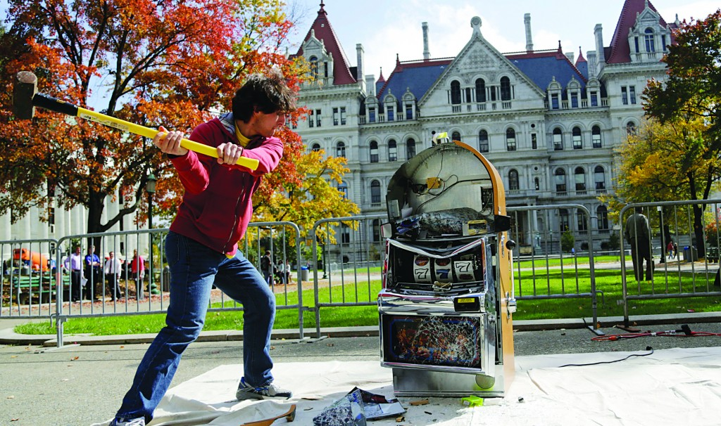 Bill Sisk of the Rockefeller Institute of Government on Tuesday, smashes a slot machine with a sledge hammer during an anti-casino event outside the state Capitol. (AP Photo/Mike Groll)