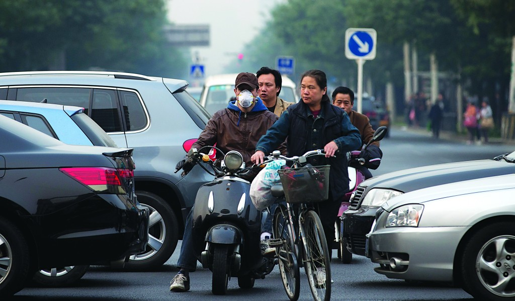 A motorcyclist wearing a mask and other cyclists ride past vehicles clogged with heavy traffic in Beijing Tuesday. Beijing is seeking to tame its smog emergencies by preparing emergency measures, such as factory shutdowns and traffic limits, to kick in when air pollution levels are high. (AP Photo/Andy Wong)