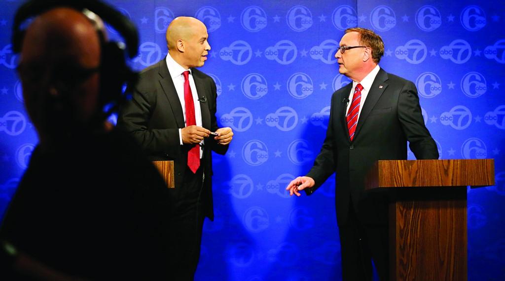 Democrat Cory Booker (L) and Republican Steve Lonegan chat before their first Senate debate in Trenton, Friday. (AP Photo/Mel Evans)