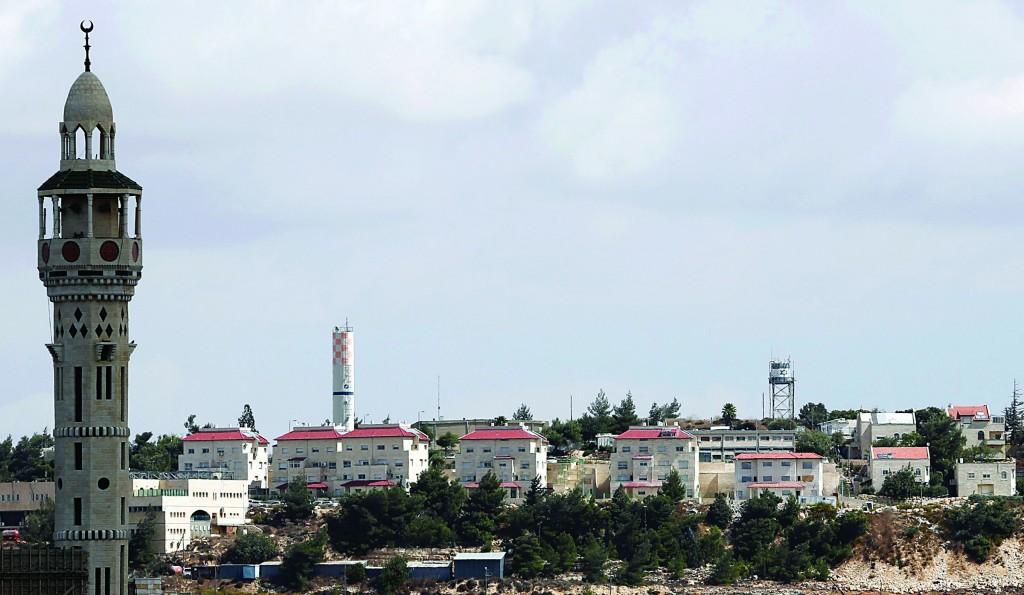 Houses in Psagot are seen behind a mosque (L) in Al-Bireh. (REUTERS/Mohamad Torokman)