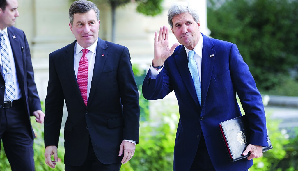 Secretary of State John Kerry (R) waves to the media as he and U.S. ambassador to France Charles H. Rivkin (L) arrive at the U.S. embassy for a meeting with the Arab League in Paris, Monday. (AP Photo/Michel Euler)