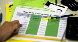 A volunteer counselor with Insure Central Texas uses a chart to help explain health insurance options in Austin, Texas. (AP Photo/Eric Gay, File)