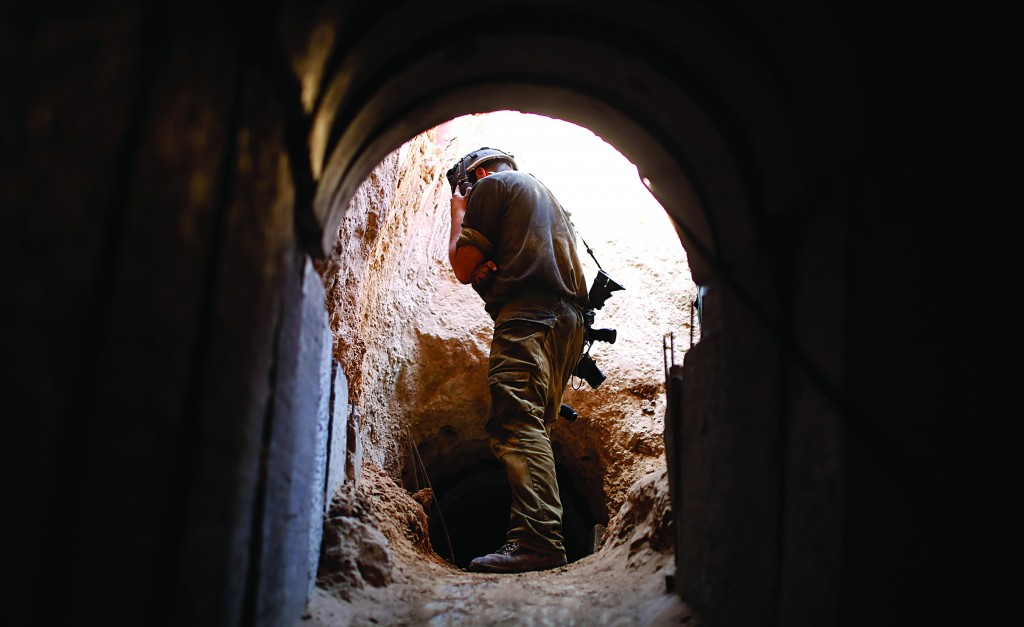 An Israeli soldier peers into a tunnel exposed by the IDF near Kibbutz Ein Hashlosha, just outside the southern Gaza Strip, on Sunday. (REUTERS/Amir Cohen)