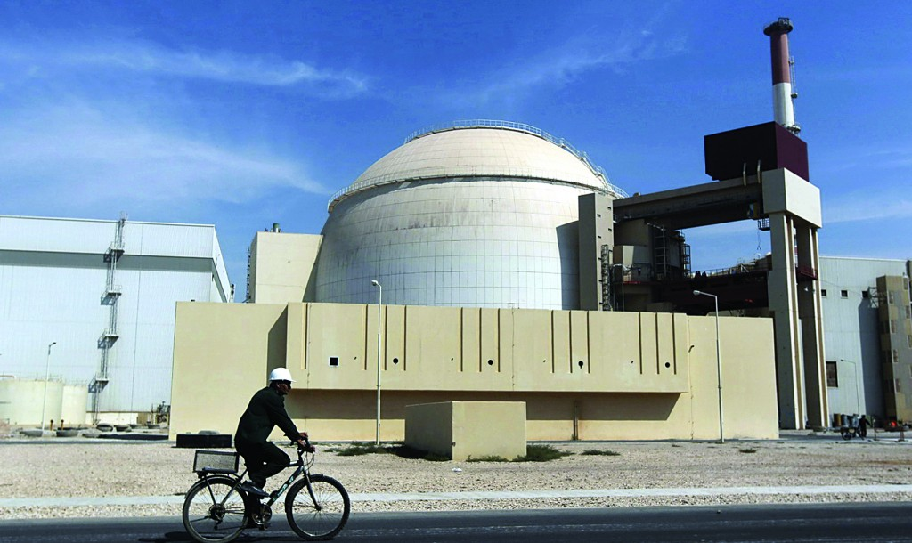 A worker rides a bicycle in front of the reactor building of the Bushehr nuclear power plant, just outside the southern city of Bushehr, Iran. (AP Photo/Mehr News Agency, Majid Asgaripour, File)