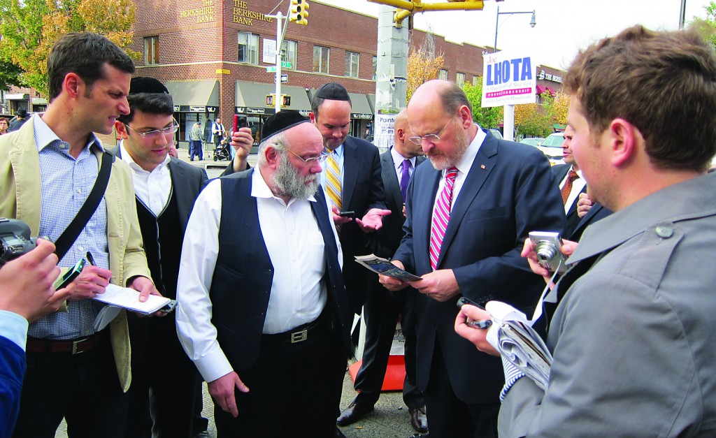A Boro Park shopkeeper talks to Joe Lhota in front of his 13th Avenue store about the difficulties of running a small business in New York City. (Yochonon Donn/Hamodia Photo)