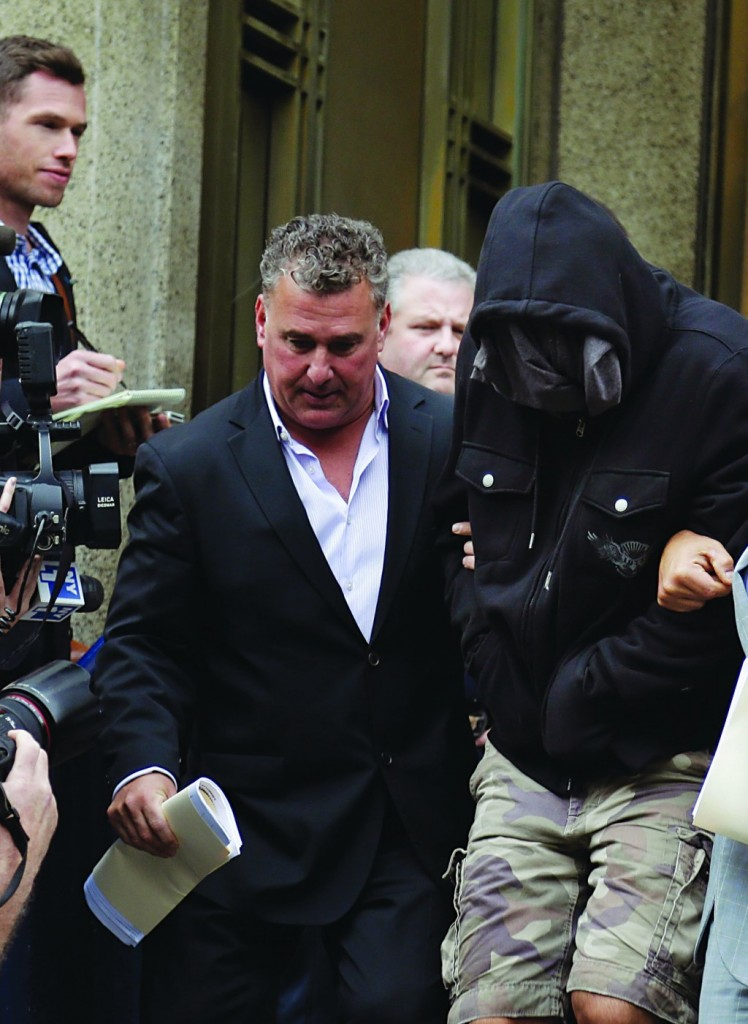 Wojciech Braszczok (R), with face covered, on Wednesday leaves the courthouse in New York following his arrest. (AP Photo/Seth Wenig)