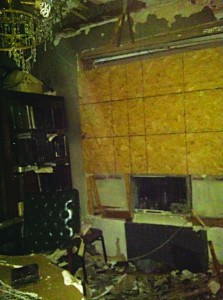 The other side of the dining room, showing Rabbi Horowitz's study area. A drenched sefarim shrank is on the left. Boards cover the window area, which FDNY broke through in order to throw out a buffet and its contents, where the leichter was still burning on the stone top.
