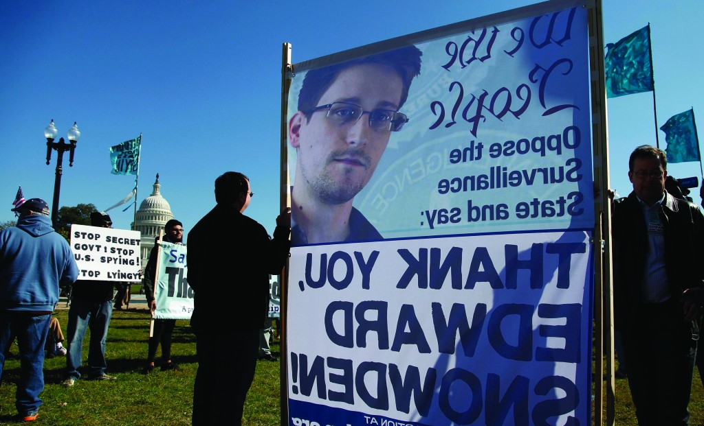 """Demonstrators hold signs supporting fugitive former NSA contractor Edward Snowden as they gather for the """"Stop Watching Us: A Rally Against Mass Surveillance"""" near the U.S. Capitol in Washington. (REUTERS/Jonathan Ernst)"""