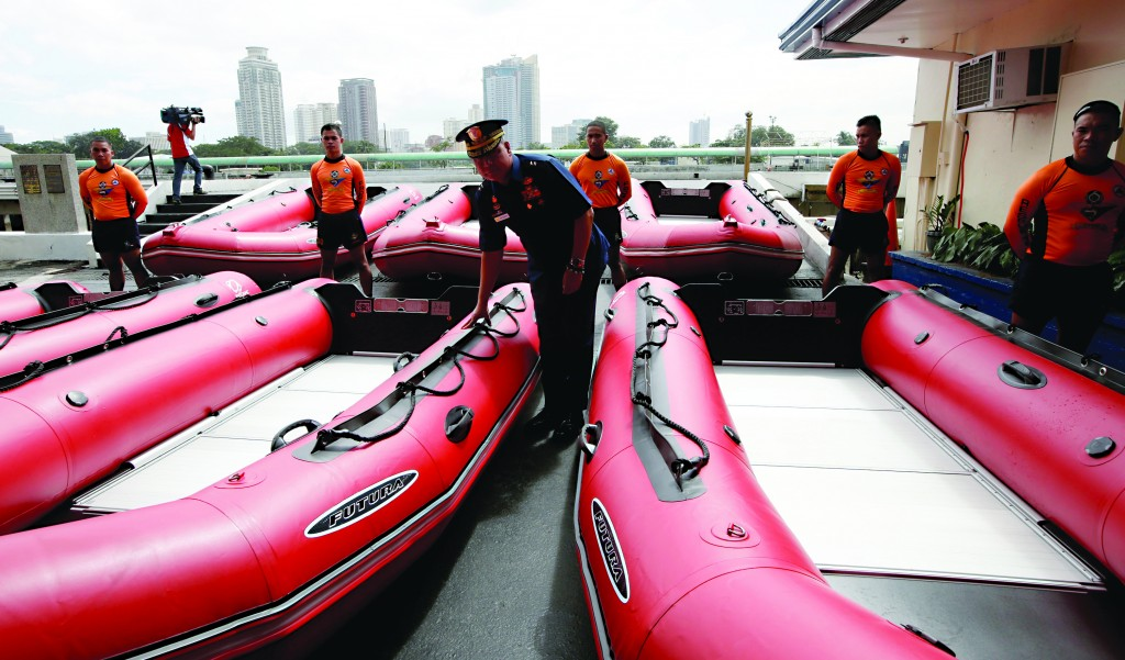 "Philippine Coast Guard Chief Rear Adm. Rodolfo Isorena checks newly-acquired rubber boats in Manila, Philippines. Isorena said the new single-hull aluminum boats and rubber boats will be deployed to central Philippines in preparation for the onslaught of super typhoon ""Haiyan."" (AP Photo/Bullit Marquez)"