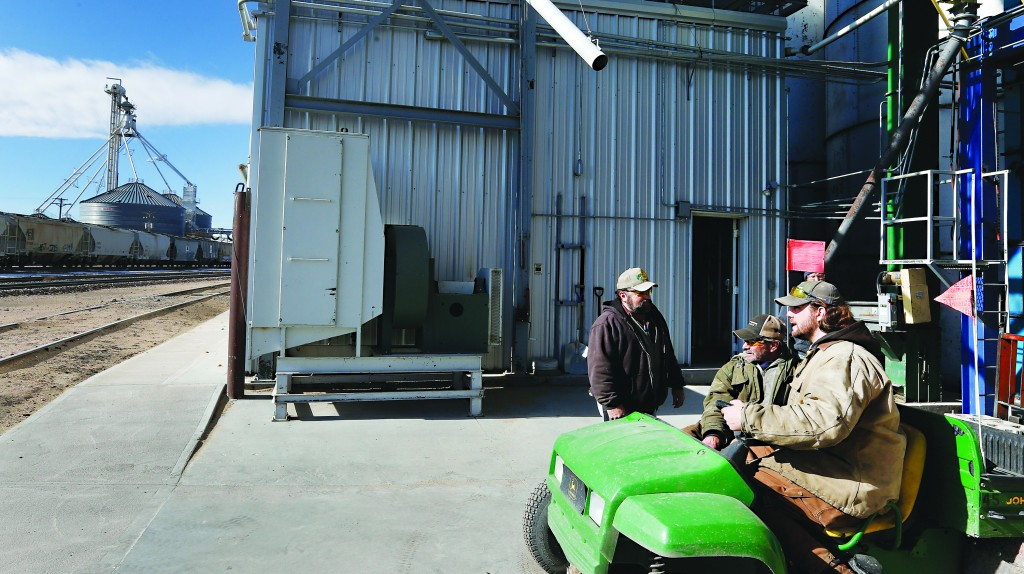Workers, left to right, Dan Dannar, Jeff Brown, and Kevin Orr talk at Global Harvest Foods, which produces birdseed and other grains, in the rural town of Akron, the county seat of Washington County, Colo. (AP Photo/Brennan Linsley)