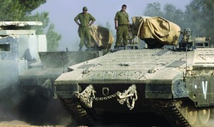 Israeli soldiers stand on top of armored personnel carriers near the border between Israel and Gaza, on Friday, Nov. 1. (AP Photo/Tsafrir Abayov)
