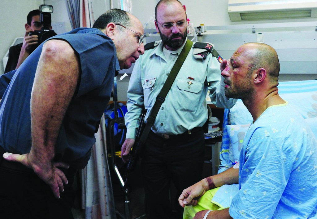 Minister of Defense Moshe Yaalon visiting one of the five Israeli soldiers wounded at a Hamas tunnel, at Soroka Hospital in Be'er Sheva on Sunday. (Ariel Hermoni/Ministry of Defense/FLASH90)