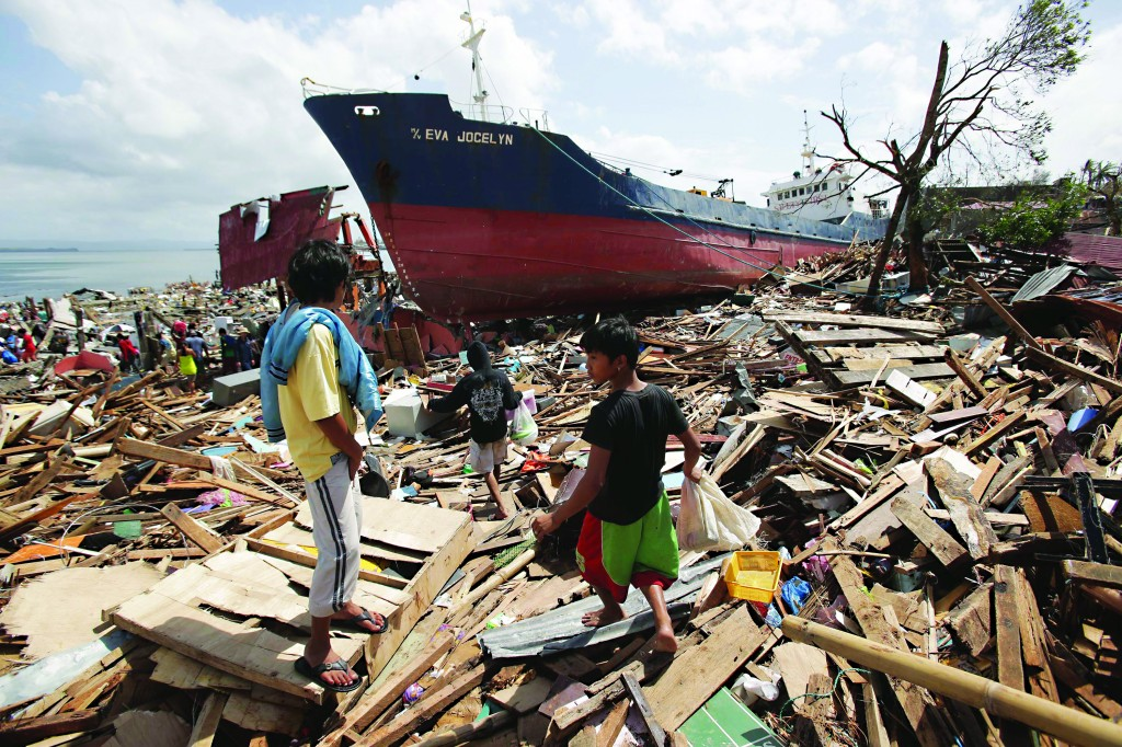 Residents walk beside a large ship that was washed ashore by strong waves caused by Typhoon Haiyan in Tacloban city, Leyte province central Philippines on Sunday, Nov. 10, 2013. (AP Photo/Aaron Favila)