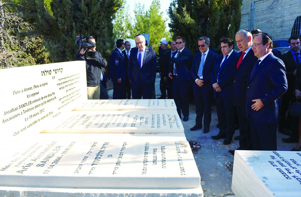 """Israeli Prime Minister Binyamin Netanyahu (second right) and French President Francois Hollande (R) at Givat Shaul cemetery in Yerushalayim, November 19, visiting the graves of the Jewish victims of a terror attack in Toulouse, France, Hy""""d. Hollande has been on a three-day official visit in Israel and the areas under Palestinian control. (Haim Zach/GPO/FLASH90)"""
