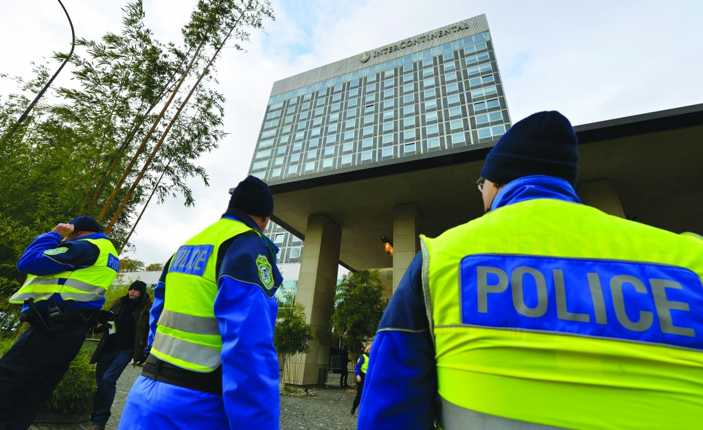 Swiss police officers control the area in front of the Intercontinental Hotel, where closed-door talks on Iran's nuclear program are taking place in Geneva, Switzerland, Thursday. (AP Photo/Keystone,Martial Trezzini)