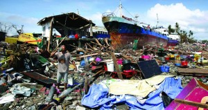 A resident drinks water beside large ships that were washed ashore by strong waves caused by Typhoon Haiyan, in Tacloban city, Leyte province, in central Philippines on Sunday. (AP Photo/Aaron Favila)
