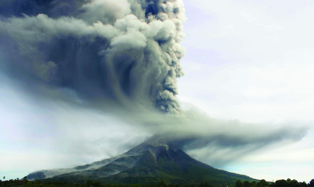 Mount Sinabung spews ash as it erupts, as seen from North Sumatra, Indonesia, Monday. Two volcanoes, Sinabung and Mount Merapi, erupted Monday in the country, prompting warnings for flights and evacuation preparations, officials said. (AP Photo/Mafa Yuli Ramadani)