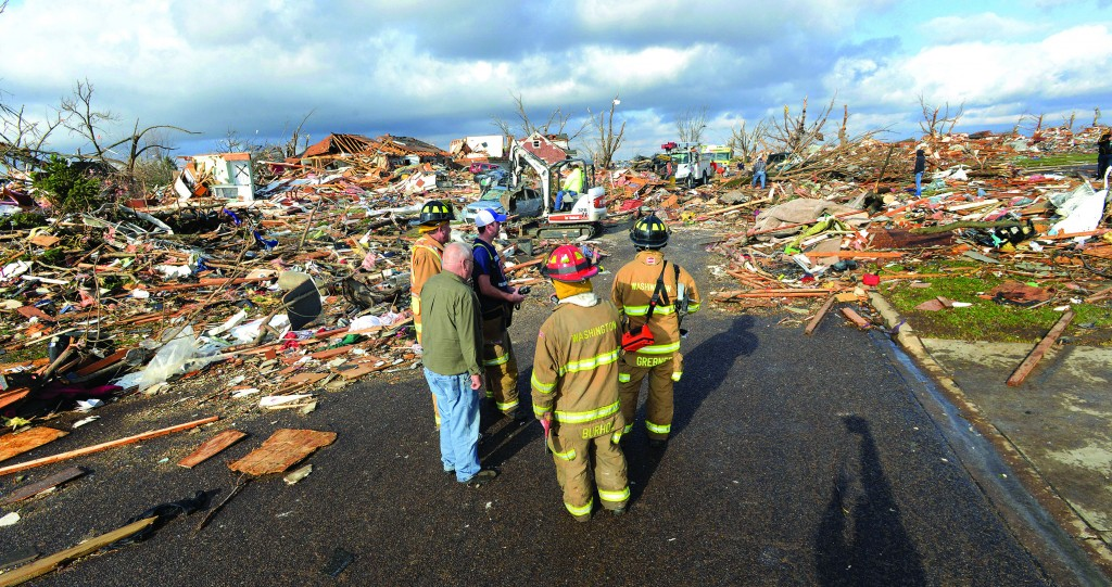 Washington, Ill., firefighters stand in the middle of Devonshire Street on the north side of the city after a tornado leveled at least 50 homes, Sunday. (AP Photo/The Pantagraph, Steve Smedley)