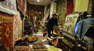 A seller arranges Iranian carpets at his shop in Dubai's old market. (REUTERS/Mohammed Omar)
