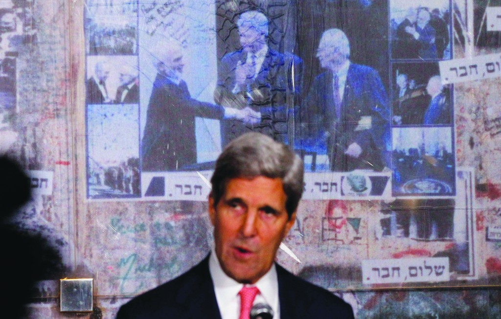 U.S. Secretary of State John Kerry is pictured in front of a photo (L-R) showing Jordan's former King Hussein, former U.S. President Bill Clinton and Israel's former Prime Minister Yitzchak Rabin, as Kerry marks the 18th anniversary of Rabin's assassination in Tel Aviv on Tuesday. (REUTERS/Jason Reed)