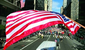 A large American flag frames Veterans Day marchers on New York's Fifth Avenue, Monday.