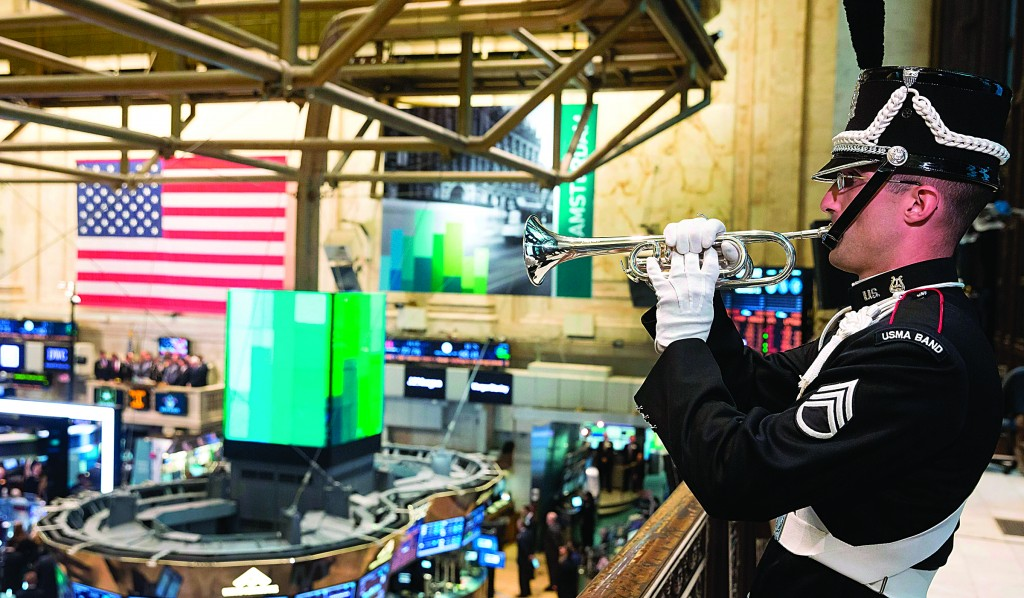 Staff Sgt. Bryan McKinney, of the U.S. Military Academy Band at West Point, on Monday plays Taps on a balcony of the New York Stock Exchange, in honor of Veteran's Day. (AP Photos)