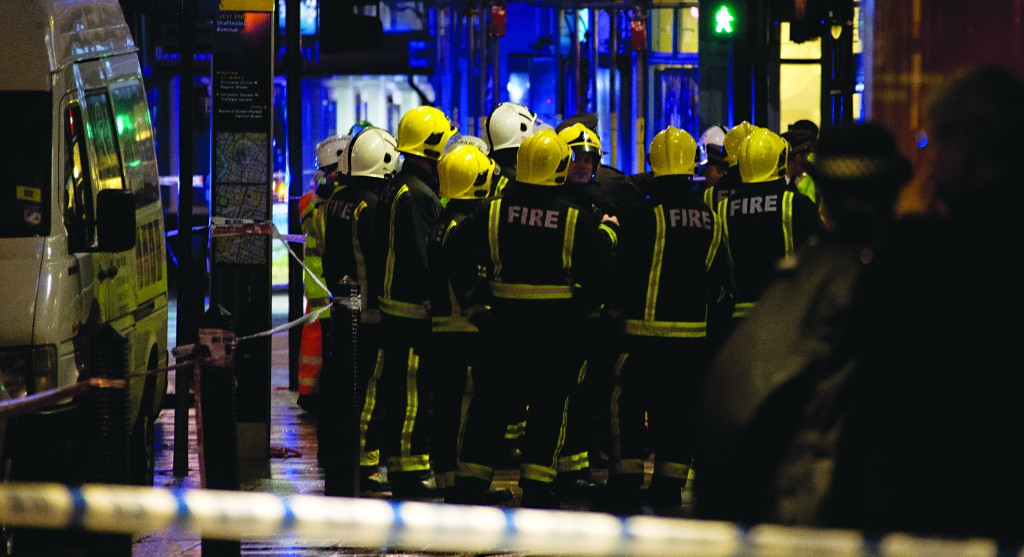 Firemen confer at the scene following an incident at the Apollo Theatre, in London's Shaftesbury Avenue, Thursday evening. (AP Photo by Joel Ryan, Invision)
