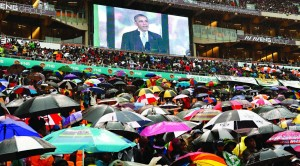 South Africans brave the rain as they listen to U.S. President Barack Obama speak during a memorial service for Nelson Mandela at FNB Stadium in Johannesburg, South Africa Tuesday. (REUTERS/Kevin Lamarque)