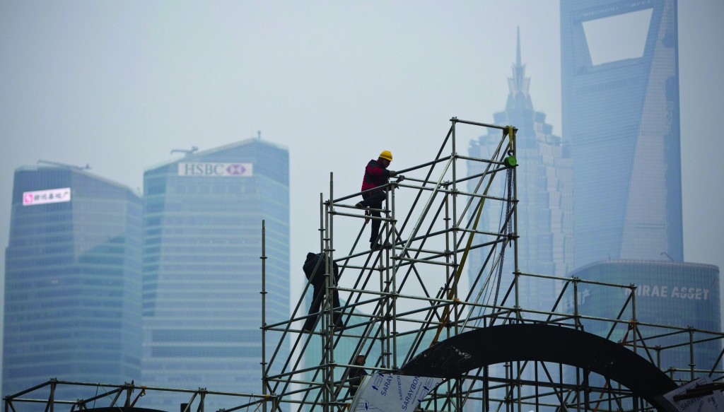 Workers install scaffolding on the Bund in front of the financial district of Pudong, during a hazy day in downtown Shanghai Tuesday. (REUTERS REUTERS/Aly Song)