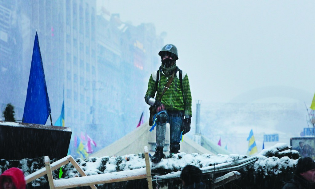 A young man stands on barricades defended by Pro-European Union activists next to the Ukrainian Government buildings in Kiev, Ukraine, Monday. (AP Photo/Sergei Chuzavkov)