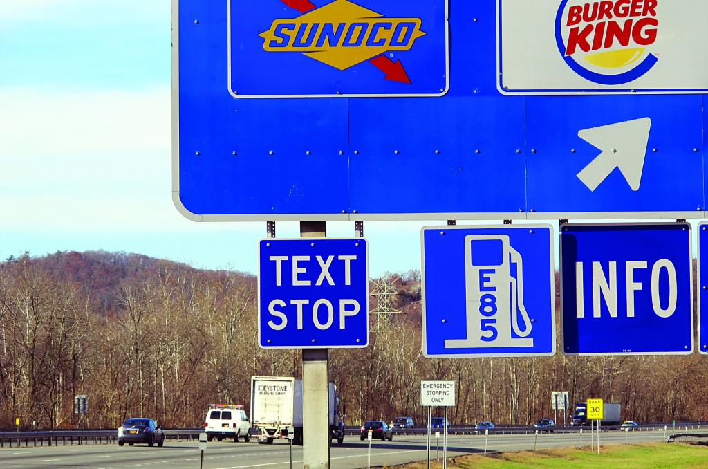 """A new """"text stop"""" notification is seen on a sign for a service area on the New York State Thruway in Sloatsburg, N.Y. A state crackdown on texting while driving includes designating many pull-off areas as text stops. (AP Photo/Jim Fitzgerald)"""