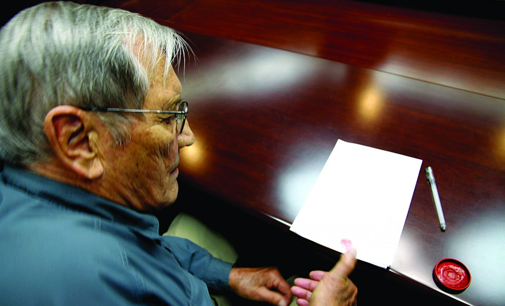 In this Nov. 9, 2013, photo released by the Korean Central News Agency (KCNA) and distributed Nov. 30, 2013, by the Korea News Service, U.S. citizen Merrill Newman, 85, applies his thumb print to a document which North Korean authorities say was an apology which Newman wrote and read in North Korea. (AP Photo/KCNA via KNS)