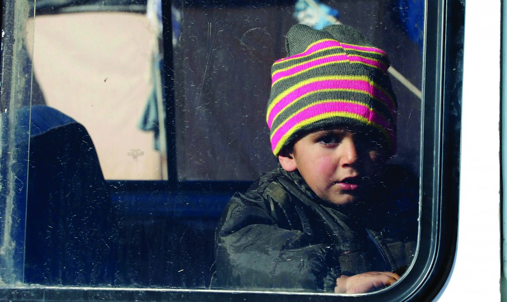 A Syrian refugee child looks out from the window of a mini-van at the Lebanese border town of Arsal, in the eastern Bekaa Valley Tuesday. The Social Affairs Ministry announced Tuesday that it started to execute a plan for helping the displaced Syrians in Lebanon amidst the snow storm expected to strike Lebanon, the National News Agency (NNA) reported. (REUTERS/Mohamed Azakir)