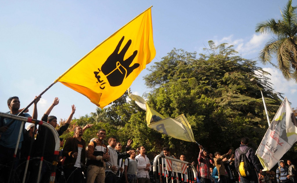 "Students of Cairo University, who are supporters of the Muslim Brotherhood and ousted Egyptian President Mohamed Mursi, wave a flag bearing the ""Rabaa"" sign during a protest against the military and interior ministry in front of at the main gate of the university in Cairo, December 9. The ""Rabaa"" sign is in reference to the police clearing of the Rabaa al-Adawiya protest camp on August 14. (REUTERS/Stringer)"