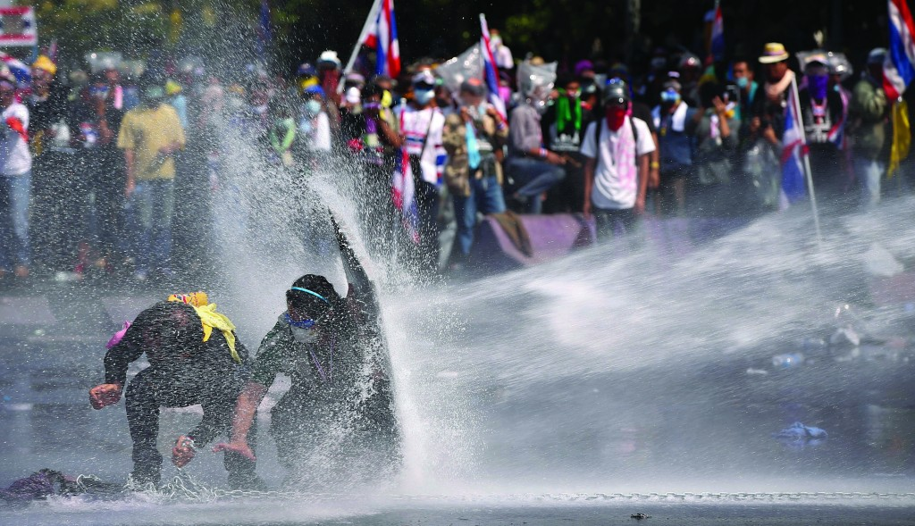 Anti-government protesters are sprayed by water cannon by police in Bangkok, Thailand, Monday. (AP Photo/Vincent Thian)
