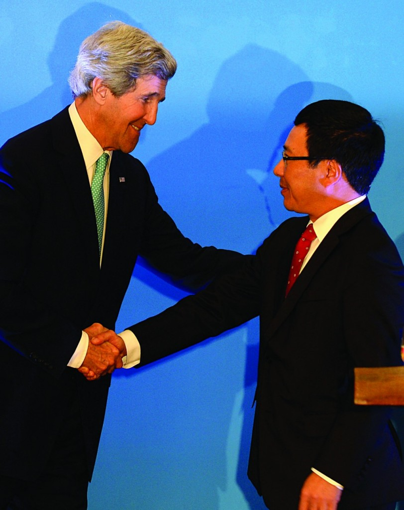 Secretary of State John Kerry (L) shakes hands with Vietnamese Foreign Minister Pham Binh Minh (R) after a joint press conference in Hanoi, Monday. (AP Photo/Hoang Dinh Nam, Pool)