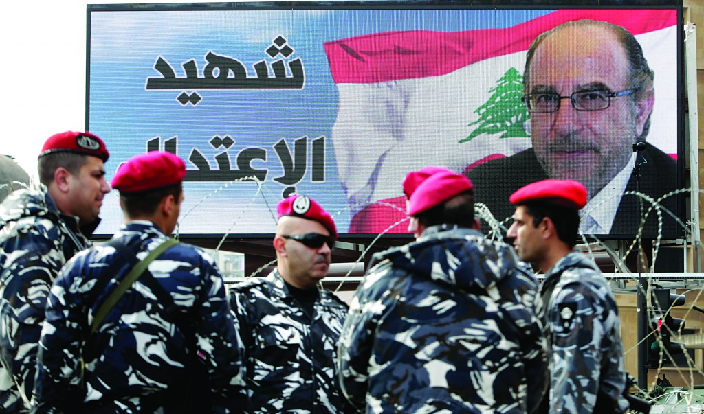 Members of the Lebanese army stand guard by a poster of Mohammed Chatah, who was assassinated on Friday by a car bomb, during his funeral procession at Mohammed at Martyrs' Square in Beirut, Lebanon, on Sunday. (AP Photo/Bilal Hussein)