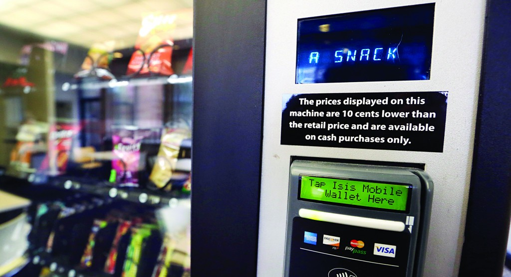 A vending machine advertises snacks on a small screen on the machine in Seattle. Office workers in search of snacks will be counting calories along with their change under new labeling regulations for vending machines included in President Barack Obama's health-care overhaul law.  (AP Photo/Elaine Thompson)
