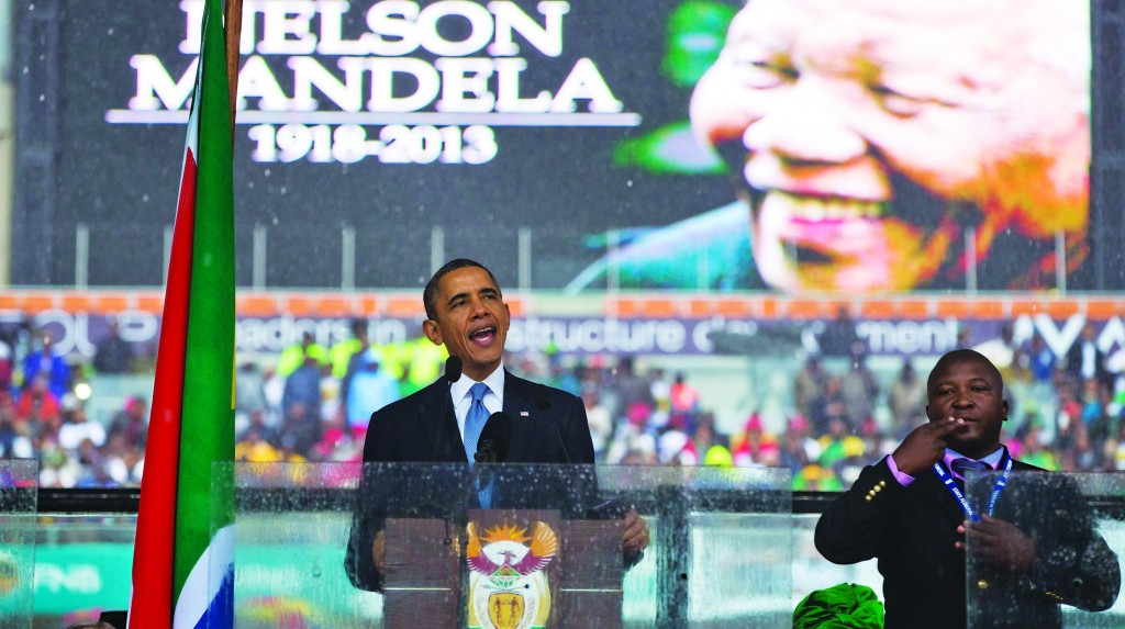 President Barack Obama delivers his speech as a sign language interpreter motions during a memorial service at FNB Stadium in honor of Nelson Mandela on Tuesday. (AP Photo/ Evan Vucci)