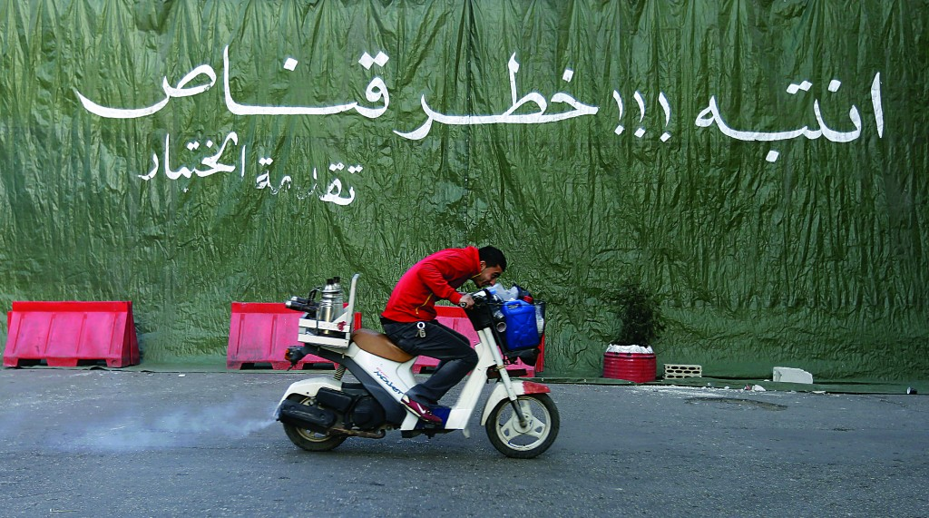 A coffee street vendor passes on his scooter in front a green tarp hung to provide cover from snipers, during clashes between supporters and opponents of Syrian President Bashar Assad in the northern port city of Tripoli, Lebanon, Monday. (AP Photo/Hussein Malla)