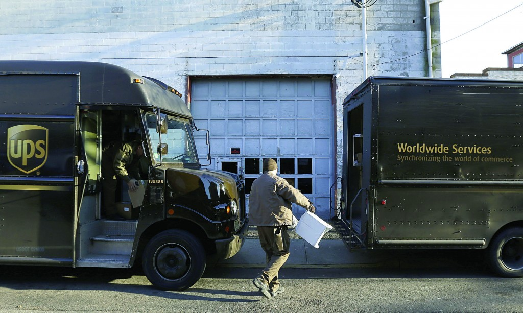 UPS delivery workers move packages from one truck to another, Thursday, in Newark, N.J. (AP Photo/Julio Cortez)