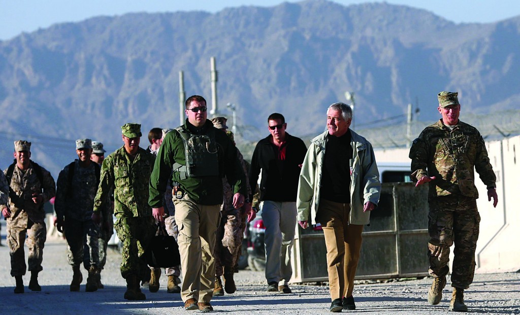 Secretary of Defense Chuck Hagel, second right, walks to speak with U.S. troops at Kandahar air base, Afghanistan, Saturday. Hagel spoke with the troops and thanked them for being deployed during the legal holiday season. (AP Photo/Mark Wilson, Pool)