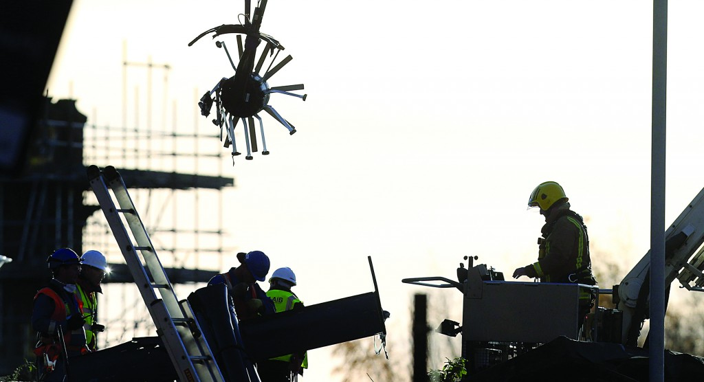 Scottish fire and rescue services look on as a section of a helicopter is lifted following its crash onto the roof of a business in Glasgow, Scotland. (AP Photo/Scott Heppell)