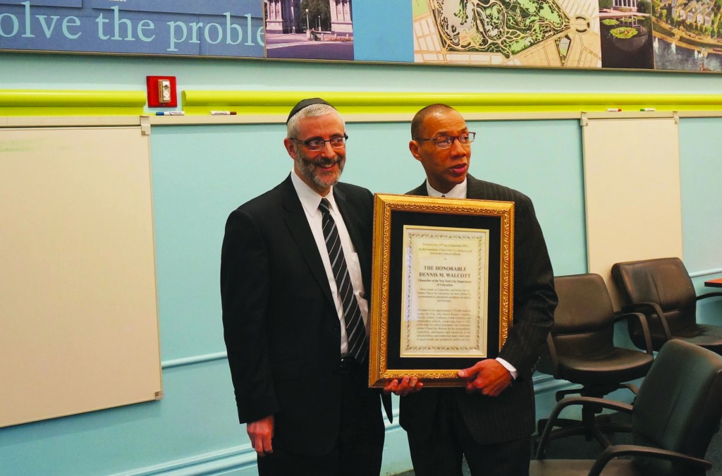 Rabbi Chaim Dovid Zwiebel on Tuesday presents a farewell plaque to outgoing New York City Chacellor Dennis Walcott. (Agudath Israel)