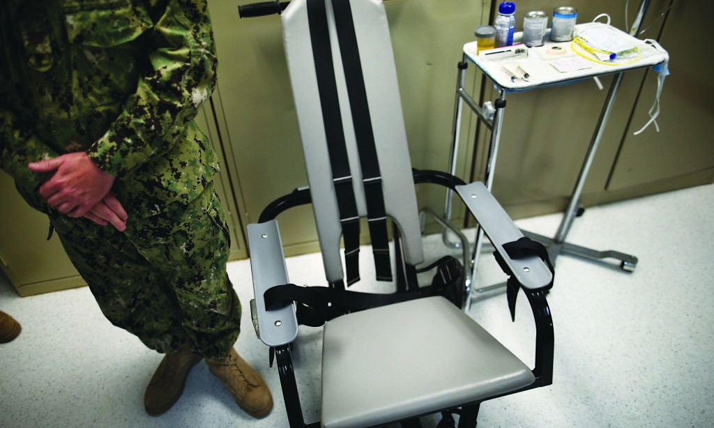 A U.S. Navy nurse stands next to a chair with restraints, used for force-feeding, and a tray displaying nutritional shakes, a tube for feeding through the nose at Guantanamo Bay Naval Base, Cuba. (AP Photo/Charles Dharapak)