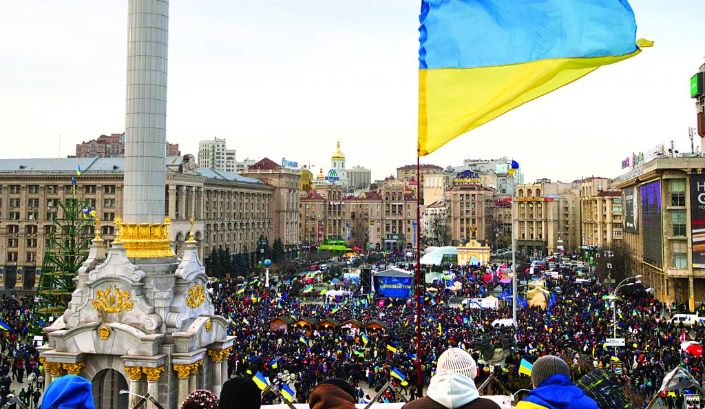 Ukrainian national flag waves as protesters rally at the central Independence Square in Kiev, Ukraine, on Tuesday. (AP Photo/Ivan Sekretarev)
