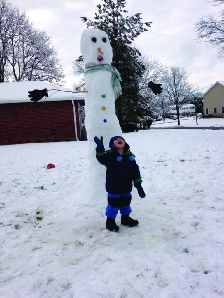 Yaakov Moshe Alyeshmerni, thankful for his day off from school yesterday, in Baltimore, Maryland, in front of his snowman.