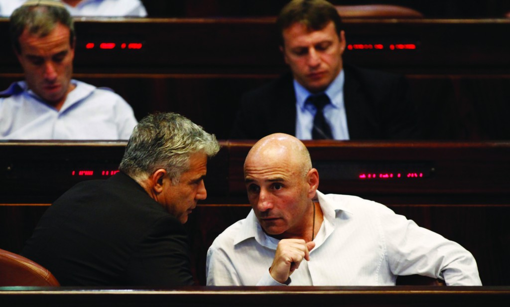 Israeli Finance Minister Yair Lapid (L) conferring with MK Ofer Shelah in the Knesset plenum. (FLASH90)