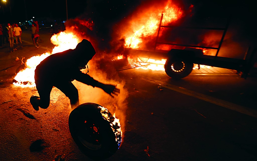 A protester rolls a burning tire toward Israeli police during a demonstration showing solidarity with Bedouin Arabs who are against a government displacement plan for Bedouins in the southern Negev Desert, in the village of Hura in southern Israel. (REUTERS/Baz Ratner)