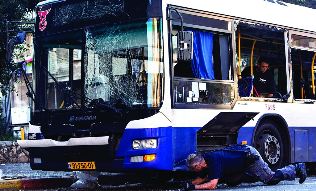Israeli police explosives experts survey a damaged bus at the scene of an explosion in the Tel Aviv suburb of Bat Yam on Sunday. (REUTERS/Nir Elias)